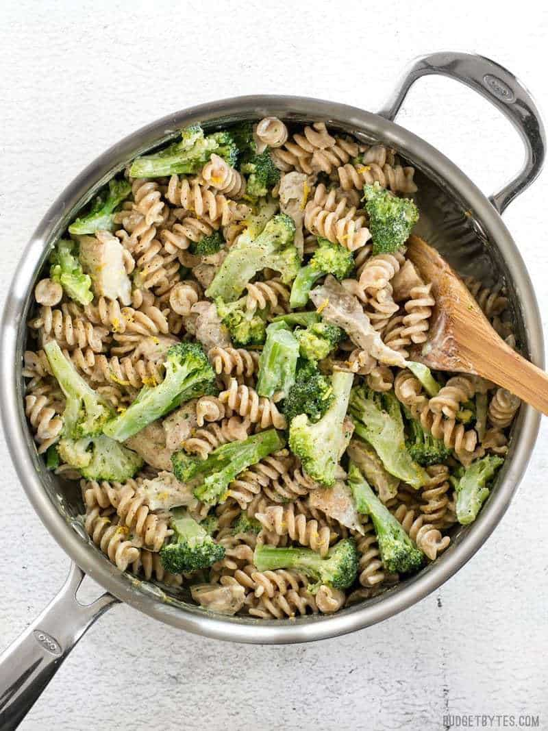 Finished Chicken and Broccoli Pasta with Lemon Cream Sauce in the skillet with a wooden spoon