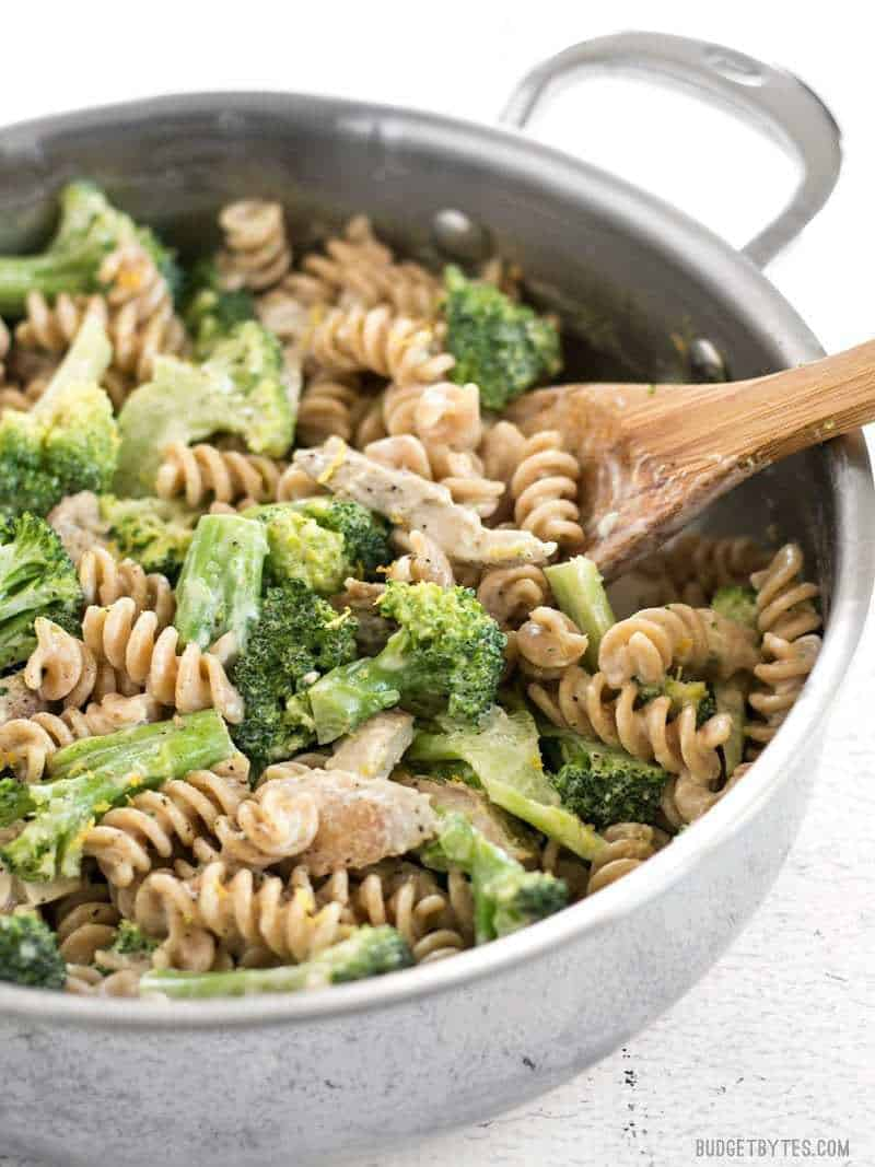 Side view of Chicken and Broccoli Pasta with Lemon Cream Sauce in the skillet with a wooden spoon