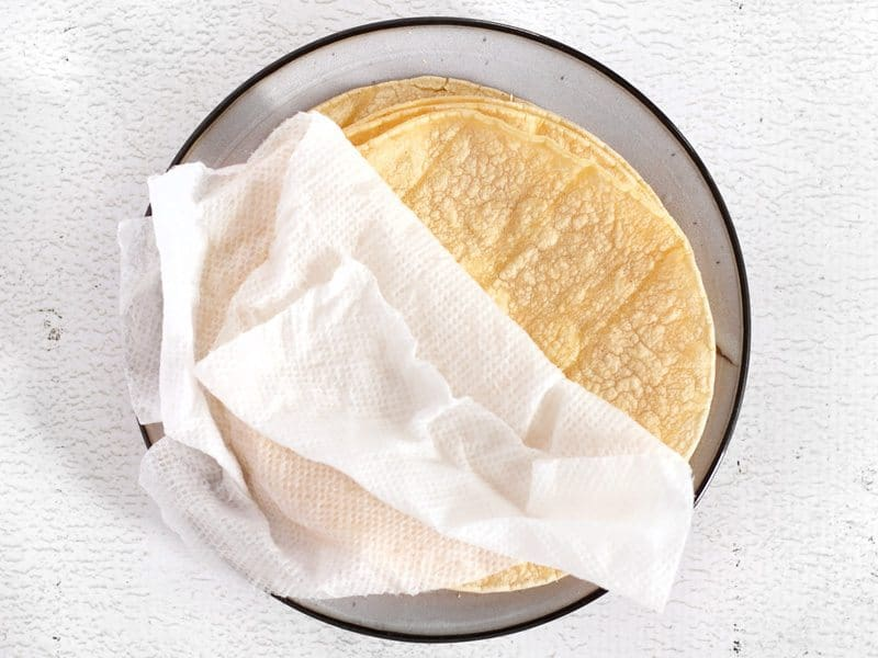 Warm Tortillas stacked on a plate with a damp paper towel on top