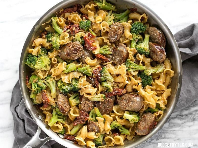 Overhead shot of One Pot Sausage and Sun Dried Tomato Pasta in the skillet with Parmesan sprinkled over top