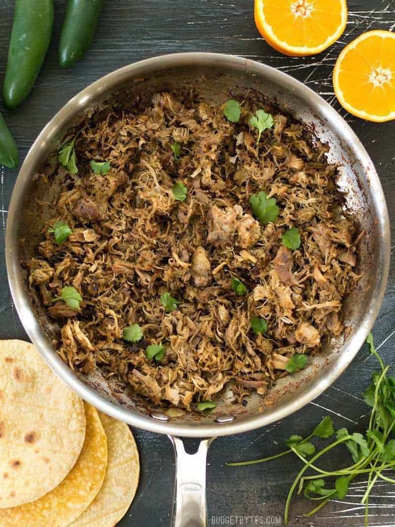 A skillet full of slow cooker carnitas with tortillas, jalapeño, oranges, and cilantro on the side