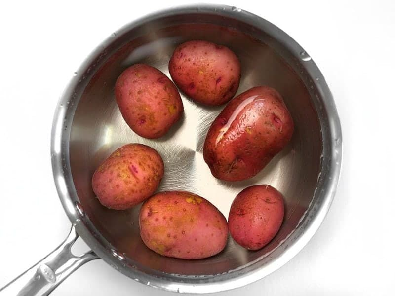 Red potatoes in a sauce pot covered with water