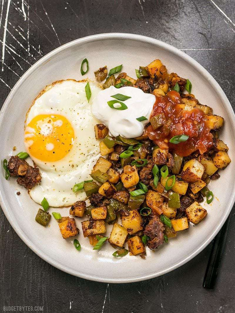 A plate full of Chorizo Breakfast Hash with a sunny side up egg, a dollop of sour cream, and salsa
