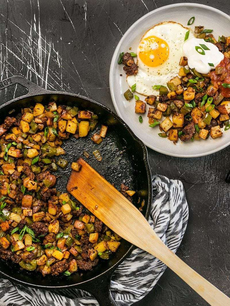 A cast iron skillet full of Chorizo Breakfast Hash next to a serving plate with a sunny side up egg