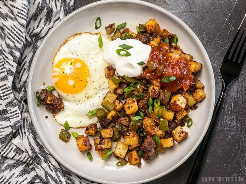 Chorizo Breakfast Hash on a plate with a sunny side up egg, sour cream, and salsa