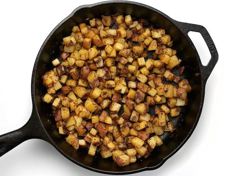 Fried Potatoes and Chili Powder in the cast iron skillet