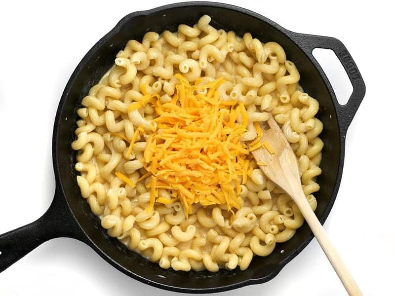 Shredded Cheese added to cast iron skillet with pasta