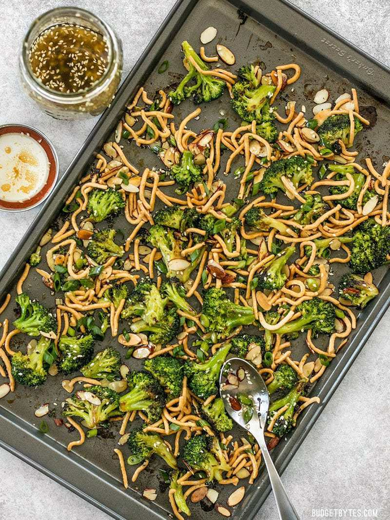 A sheet pan full of Roasted Broccoli Salad with Almonds and a jar of Simple Sesame Dressing on the side