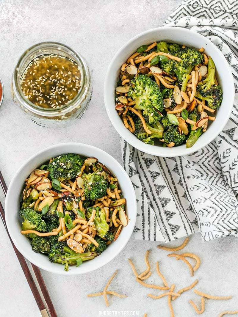 Two bowls of Roasted Broccoli Salad with Almonds with a jar of Simple Sesame Dressing on the side