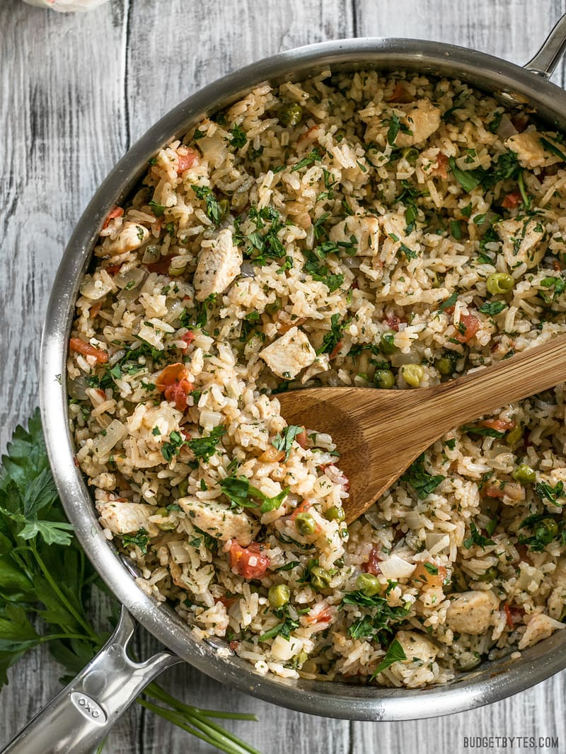 Chimichurri Chicken and Rice in the skillet with a wooden spoon