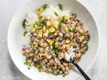 These rich and spicy Coconut Jerk Peas are super simple to make and pair brilliantly with a sweet and vibrant pineapple salsa. BudgetBytes.com