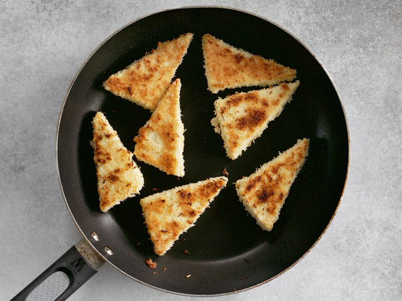 Fry coconut crusted tofu triangles in a skillet