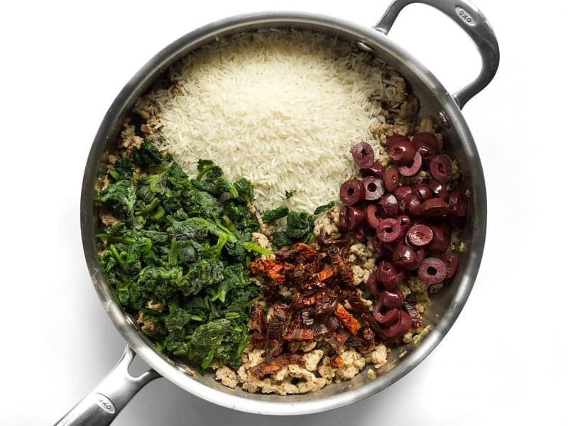 Add rice, spinach, olives, and sun dried tomatoes to skillet