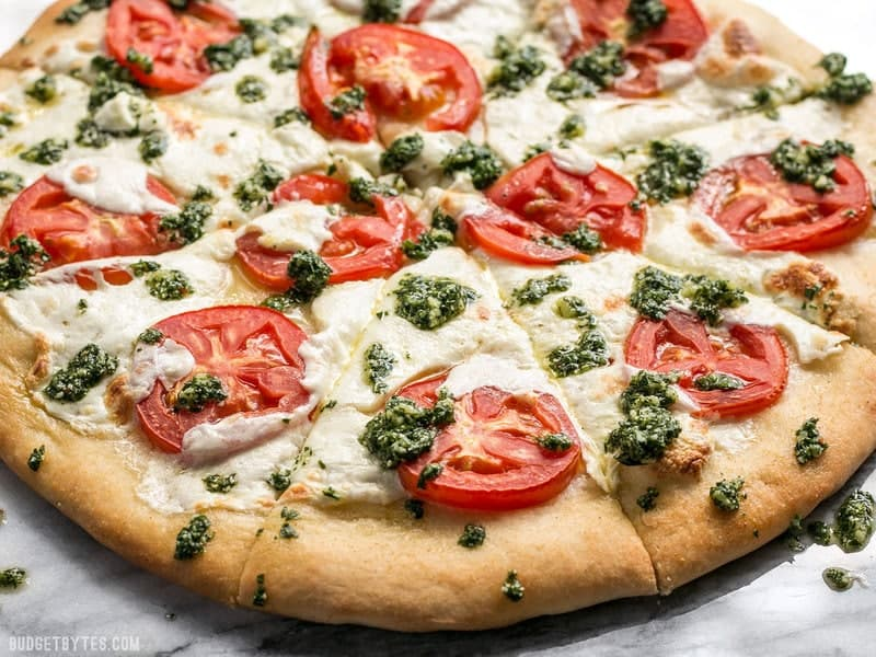 Take your Marghertia pizza up a level with a drizzle of zesty parsley pesto. This white pizza is anything but boring. BudgetBytes.com