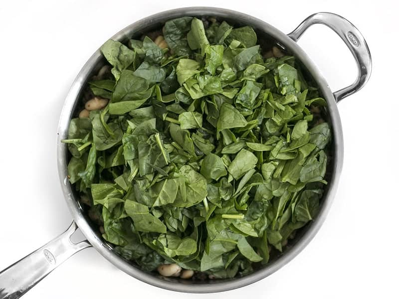 Add Spinach to skillet with sausage and white beans