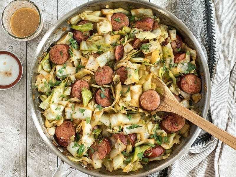 Bird's eye view of Kielbasa and Cabbage Skillet with a jar of tangy mustard vinaigrette.