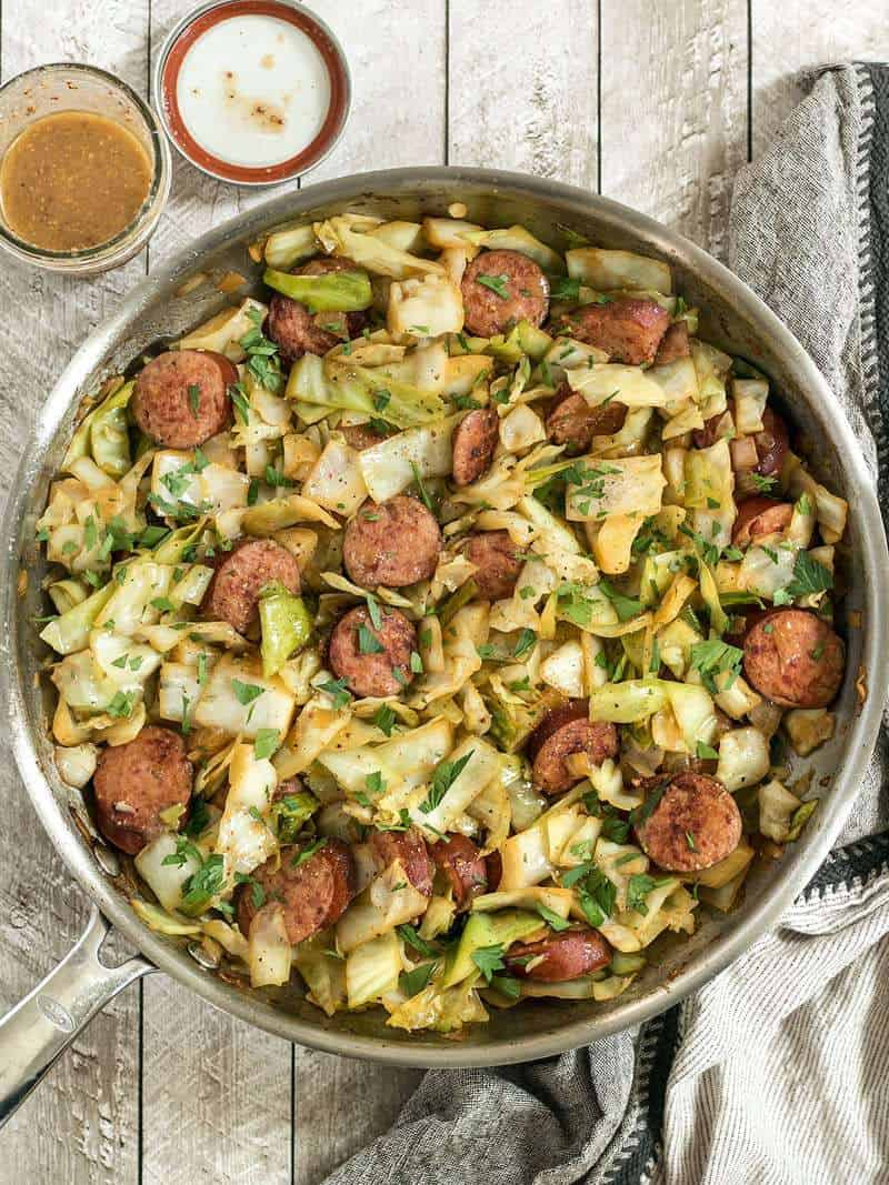 A full pan of Kielbasa and Cabbage Skillet with a jar of tangy mustard vinaigrette by its side.