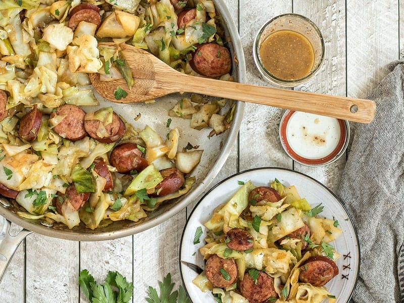 Kielbasa and Cabbage Skillet being served onto a plate from the skillet, with mustard vinaigrette in a jar on the side.