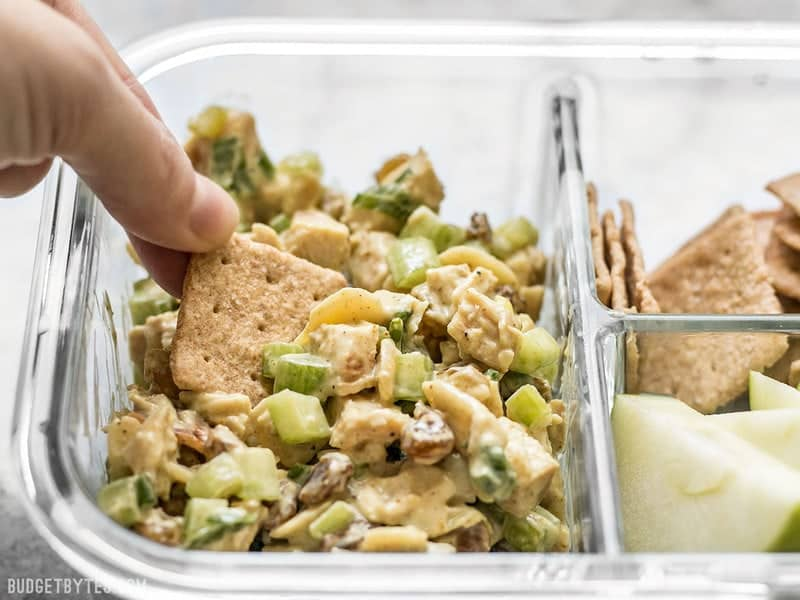 A cracker being dipped into Curry Chicken Salad in the meal prep container