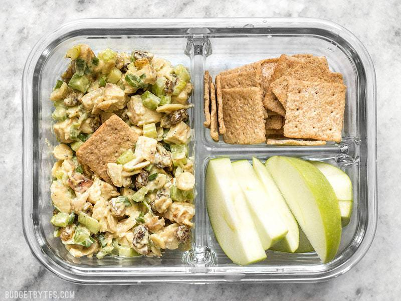 A single Curry Chicken Salad meal prep container with crackers and apples