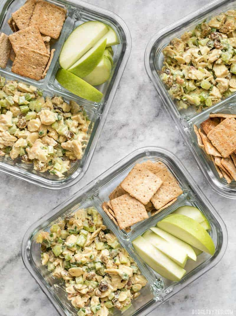 Curry Chicken Salad meal prep containers scattered on a surface