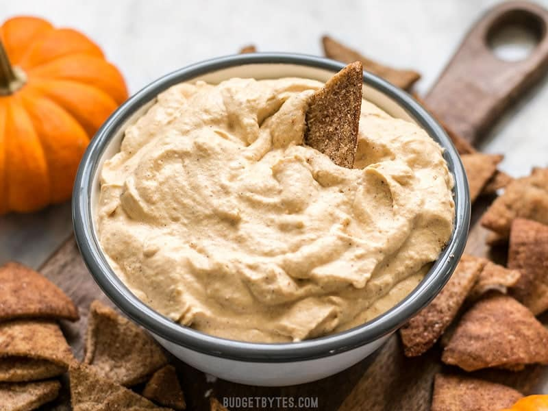 Front view of a Cinnamon Pita Crisp being dipped into a bowl of fluffy Pumpkin Cheesecake Mousse