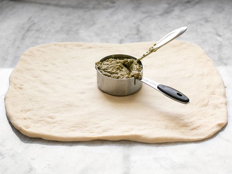 Square Pizza Dough with a measuring cup full of pesto on top
