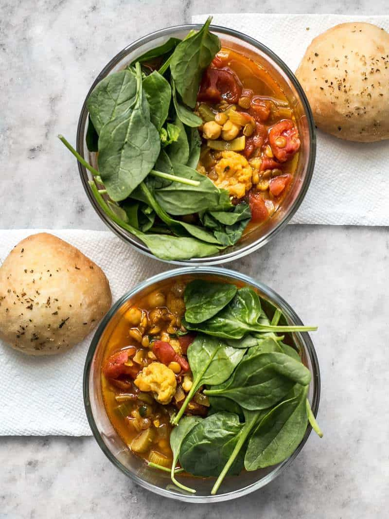 Two meal prep bowls with Moroccan Lentil and Vegetable Stew topped with spinach and a focaccia roll for each