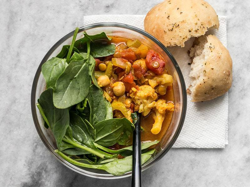 One bowl of Moroccan Lentil and Vegetable Stew with spinach and a focaccia roll