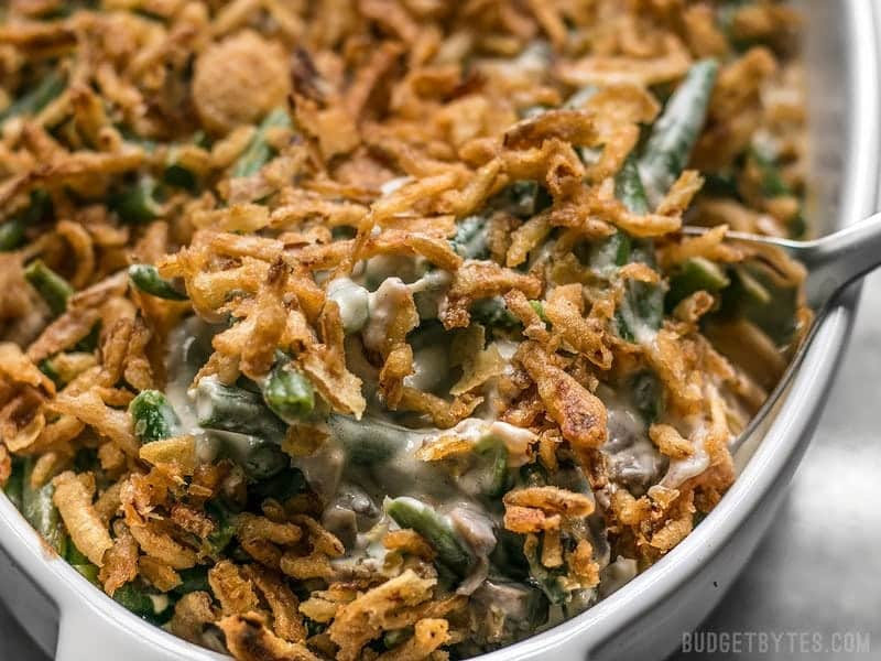 Close up view of the Creamiest Green Bean Casserole, made with whole green beans and topped with crispy fried onions.