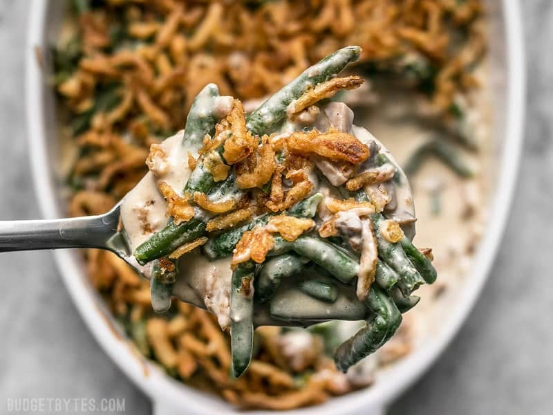 A spoonful of the Creamiest Green Bean Casserole, made with no canned soup, and topped with crunchy fried onions.