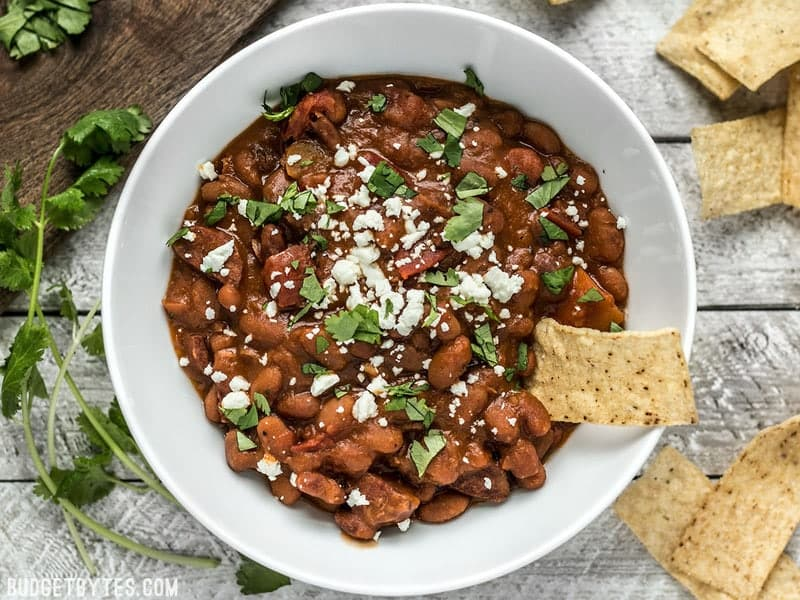 Overhead view of Instant Pot Pinto Beans with Chorizo, topped with cheese and cilantro