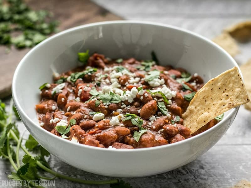 Side view of a bowl of Instant Pot Pinto Beans with chorizo. Topped with cheese and cilantro.
