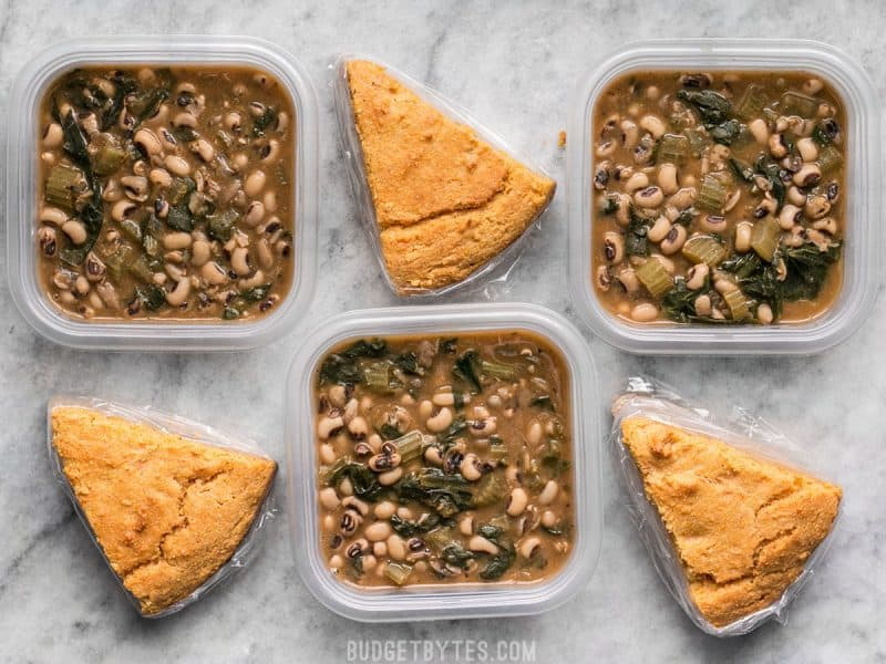 Three Black Eyed Peas Meal Prep containers alternating with cornbread slices