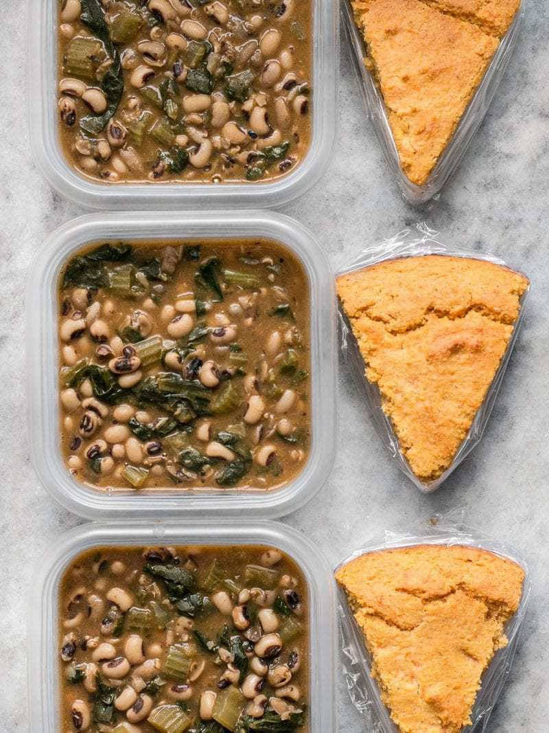 Three Black Eyed Peas Meal Prep containers in a row with cornbread slices on the side