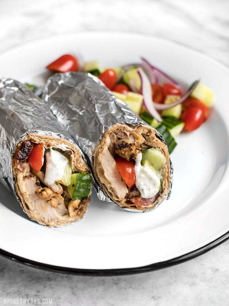 Greek Chicken Wraps wrapped in foil on a plate with salad