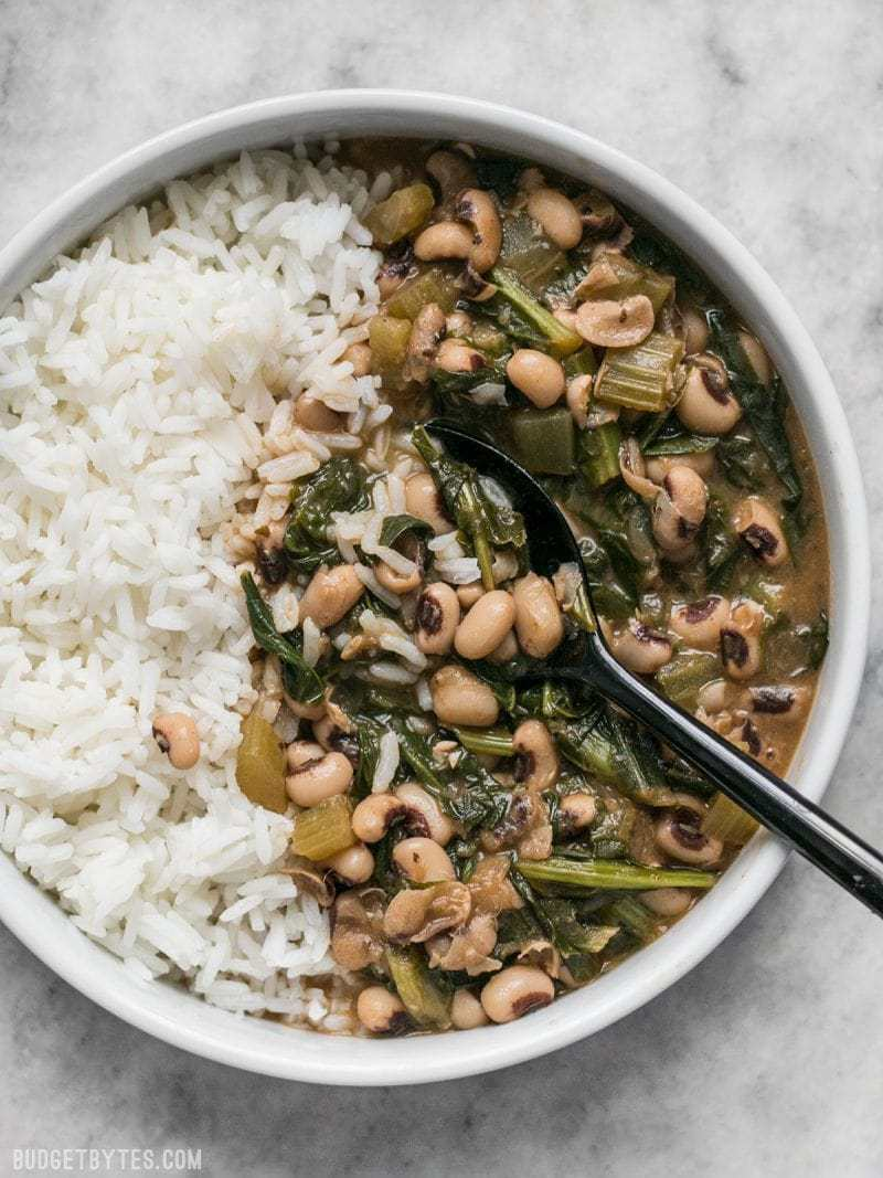 A large bowl of Slow Simmered Black Eyed Peas with Greens, served with rice.