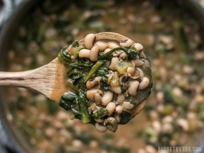A ladle full of Slow Simmered Black Eyed Peas with Greens
