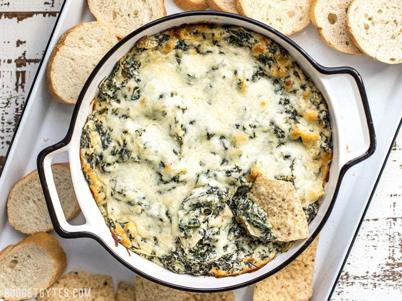 Overhead view of Double Spinach Artichoke Dip in a casserole dish surrounded by bread and tortilla chips