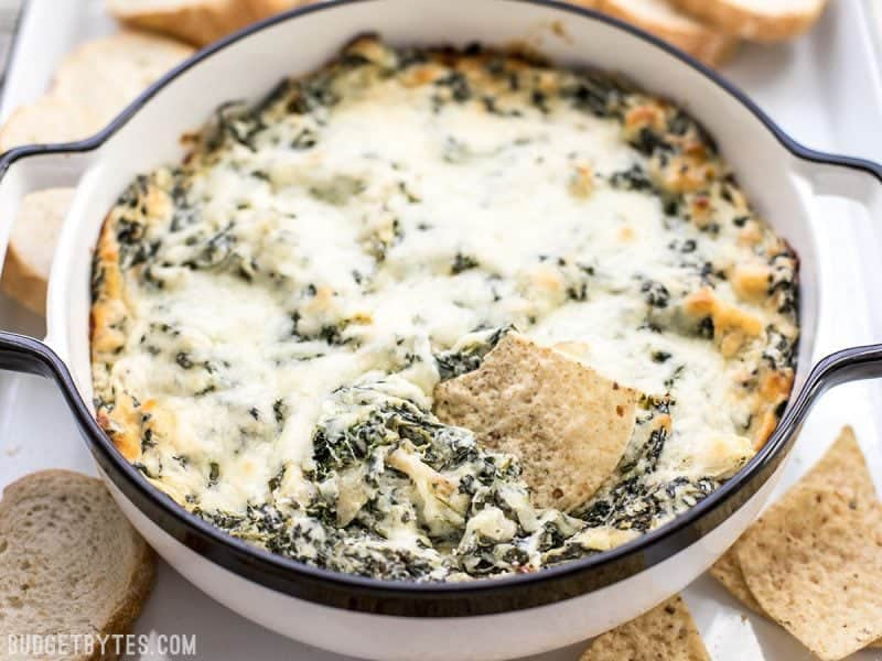Front view of casserole dish with Double Spinach Artichoke Dip with a dipped tortilla chip
