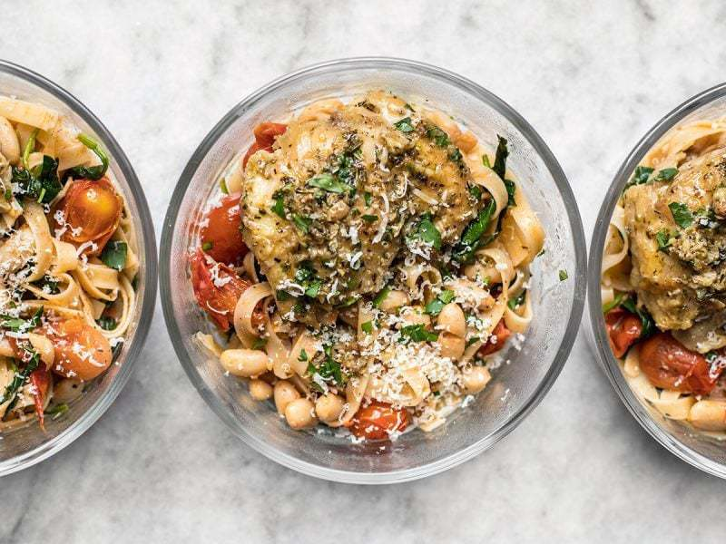 Glass meal prep containers lined up with Herb Butter Chicken and tuscan white bean pasta