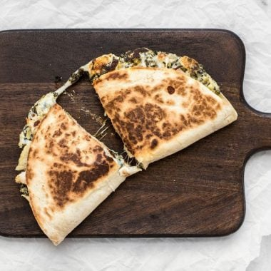 Use your leftover party dips to make a delicious lunch the next day, like these super creamy Spinach Artichoke Quesadillas. BudgetBytes.com