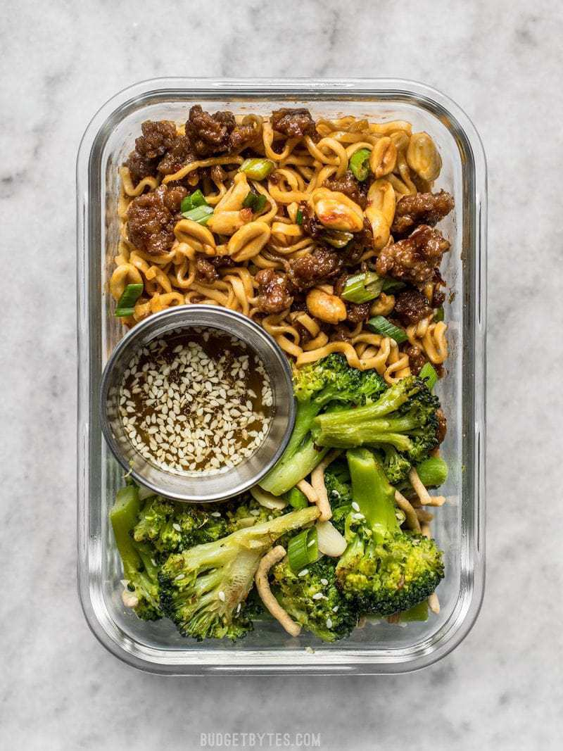 A glass meal prep container with Pork and Peanut Dragon Noodles and Broccoli Salad