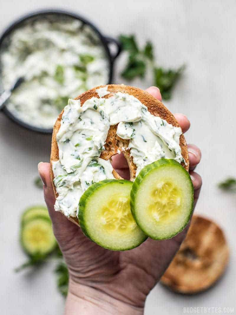 A hand holding a toasted bagel smeared with Scallion Herb Cream Cheese Spread and a couple of cucumber slices