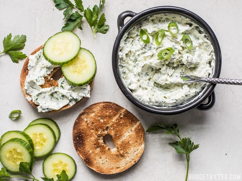 A bowl of Scallion Herb Cream Cheese Spread next to a toasted bagel with cucumber slices