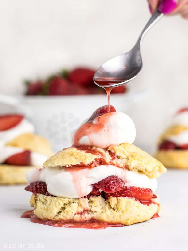 Strawberry syrup being drizzled over Strawberry Shortcake
