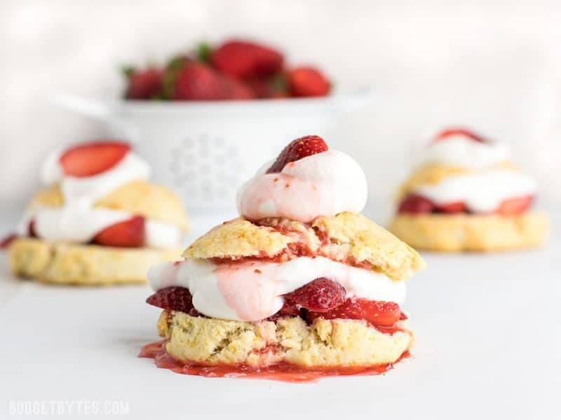Three Strawberry Shortcakes with strawberry juice drizzled over top