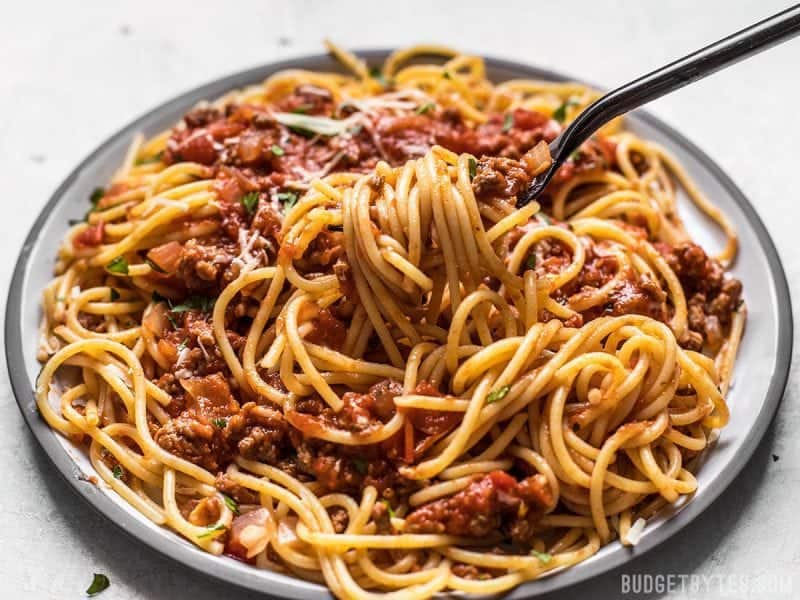A fork lifting spaghetti with The Best Weeknight Pasta Sauce off the plate