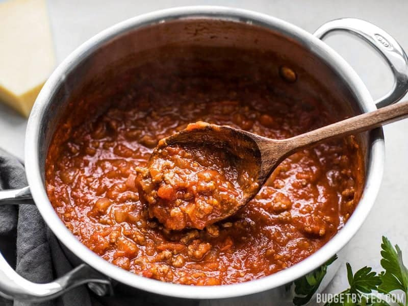 Close up of a spoon scooping The Best Weeknight Pasta Sauce out of the pot