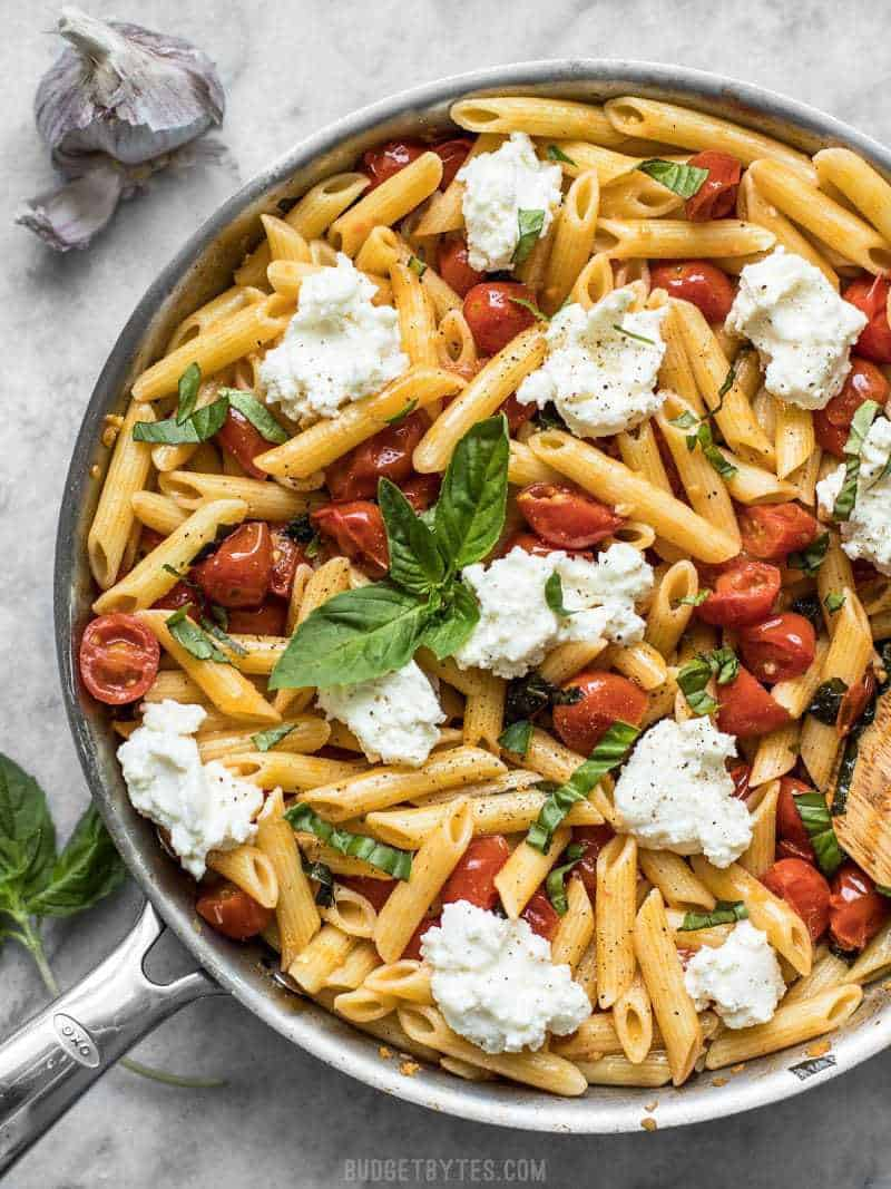 A skillet full of Fresh Tomato Basil Pasta with Ricotta. Fresh basil on top, garlic on the side.